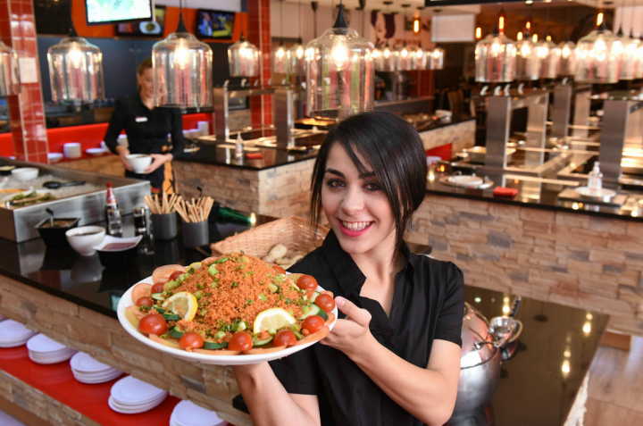 Four Corners employee Meena with one of the many dishes on offer at the restaurant.